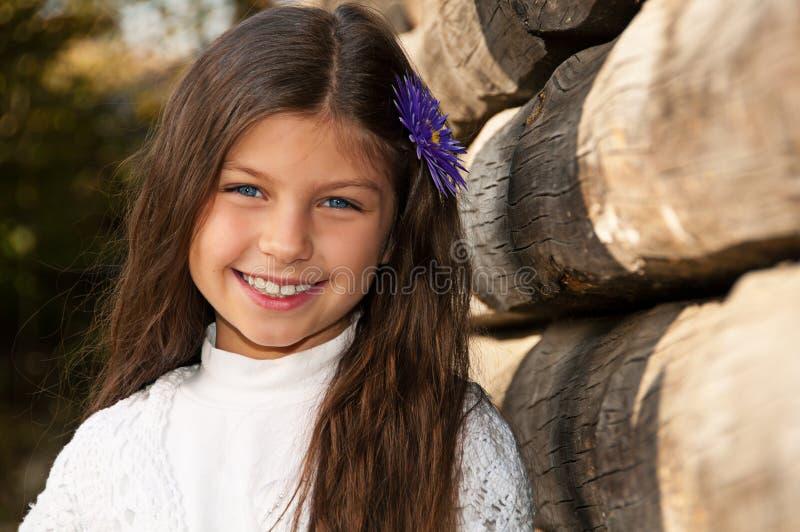 Przeciw drewnianemu ogrodzeniu długowłosa uśmiechnięta dziewczyna obraz royalty free