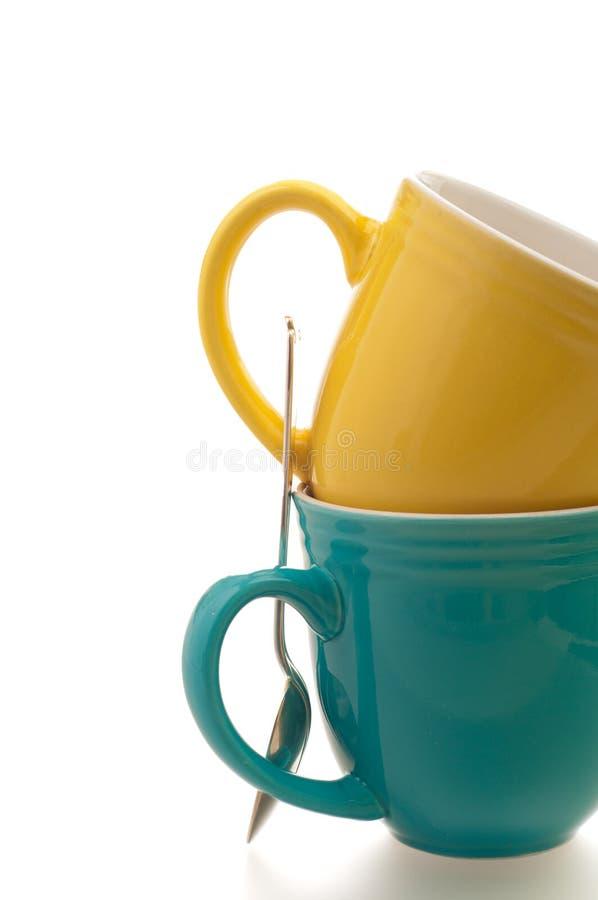 przeciw kawowemu kolorowemu kubków łyżki biel zdjęcia stock