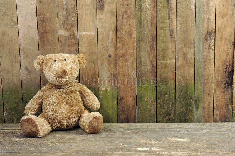 przeciw niedźwiedziowi drewniana miś pluszowy sadzająca ściana obrazy stock