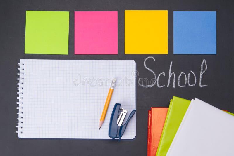 Przeciw tłu czarna deska z wpisową szkołą, są tematy dla nauki, kolorowi majchery, notatnik, książki, zdjęcia royalty free