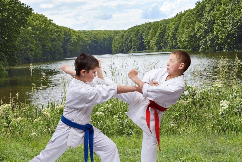Przeciw tłu natura dwa chłopiec trenują cios nogę i rękę obraz royalty free