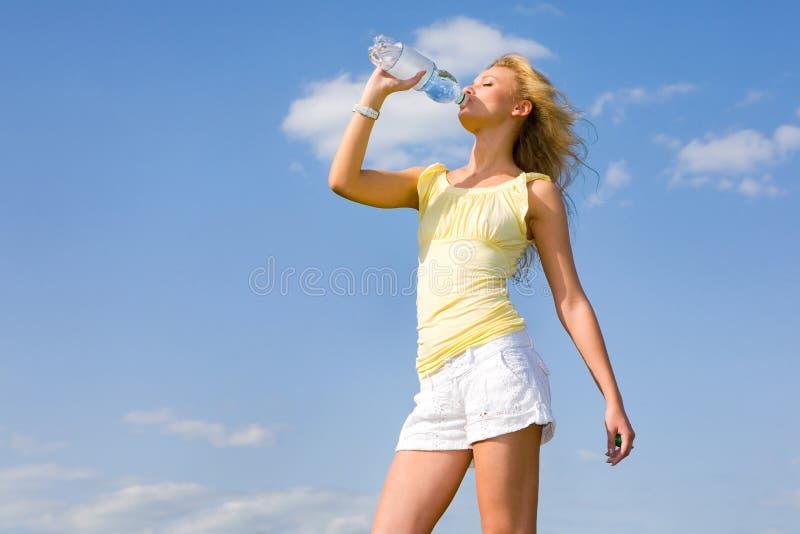 przeciwko piękną niebieskiej pije nieba wodzie dziewczynę zdjęcie royalty free