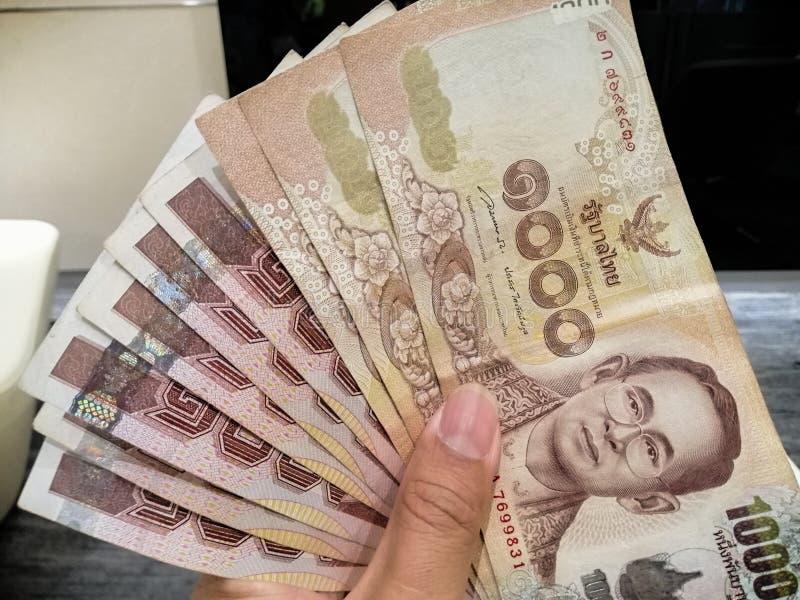 Przedkłada Tajlandzkich banknoty dla zapłaty - banknotu 1000 baht Tajlandzki w ręce, królewiątko Rama 9 na Tajlandzkim pieniądze zdjęcie royalty free