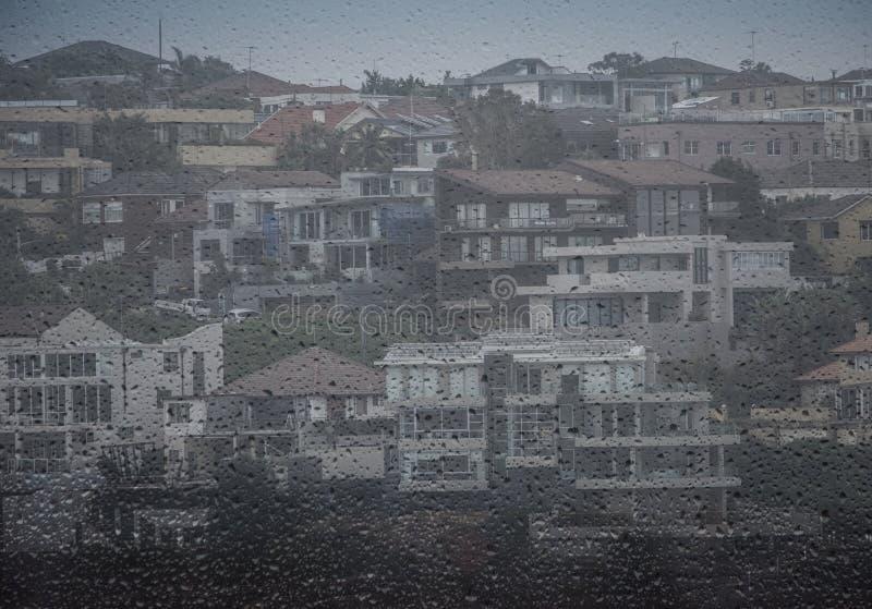 Przedmieścia przez okno raindrops zdjęcie royalty free