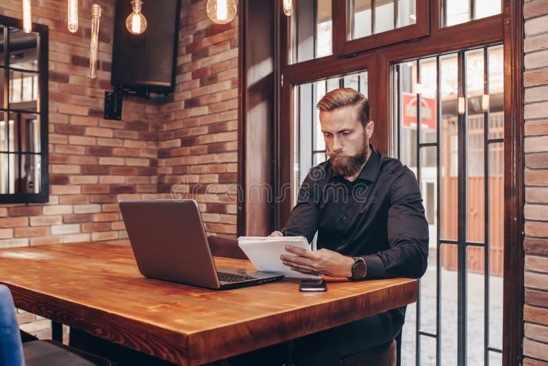 Przedsiębiorca pracuje z laptopem i trzyma dokument obraz stock
