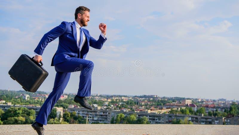 Przedsiębiorca w ruchu zdecydowanym wyrażeniu Biznesmena formalny kostium niesie teczki nieba tło Biznesmen obraz royalty free