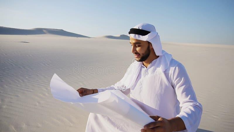 Przedsiębiorczy męski sheikh biznesmena obsiadanie z białym papierem wewnątrz obrazy royalty free