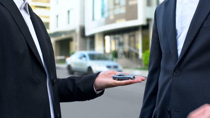 Przedstawicielstwo firmy samochodowej sprzedawca przedstawia symbolicznego zabawkarskiego samochód klient, kupuje pojazd zdjęcie stock