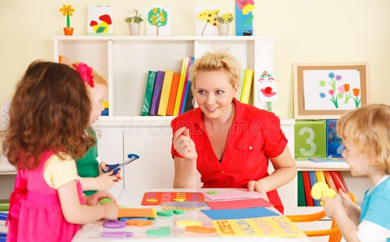 Przedszkolni dzieci w sala lekcyjnej z nauczycielem zdjęcia royalty free