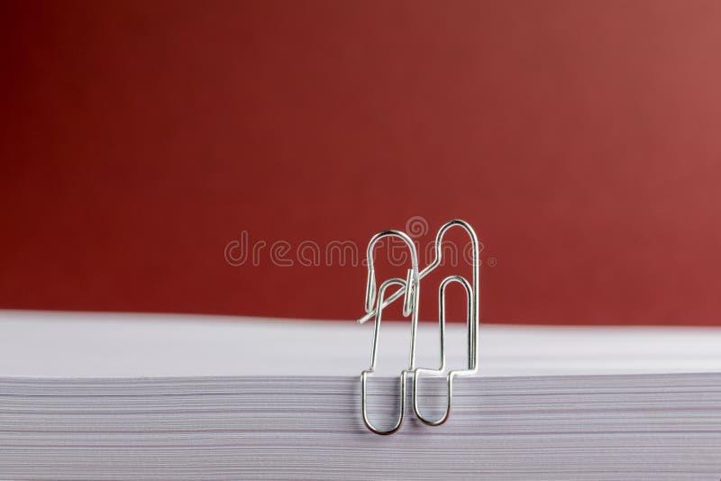 Przegięte papierowe klamerki Cuddling na białej księdze na Czerwonym tle fotografia royalty free