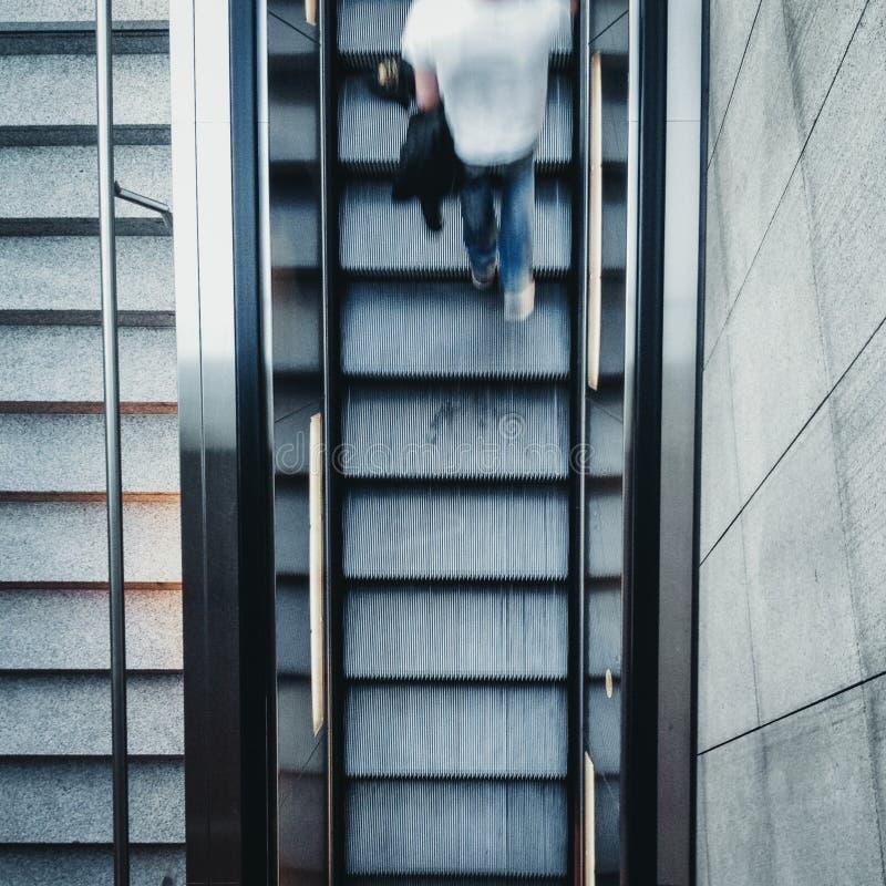 Przegląda od above na szybkim poruszającym młodym człowieku chodzi w górę eskalatoru schodków zdjęcie royalty free