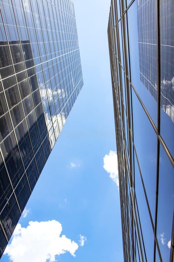 Przegląda pozycję między dwa wysokimi szklanymi drapaczami chmur patrzeje prosto up przy budynkami odbija each inny i niebo - per zdjęcia stock