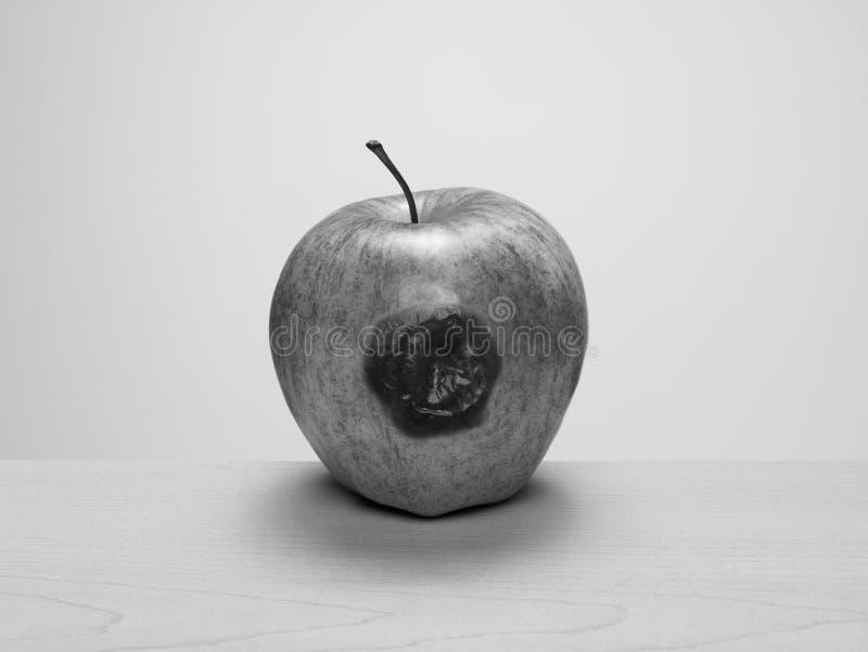 Przegniły sedno, posiniaczony jabłko na drewno stole zdjęcie royalty free