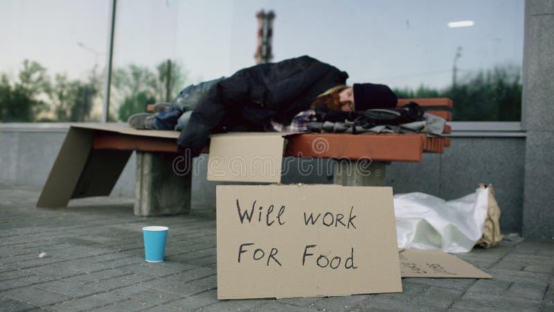 Przegrany młody bezdomny mężczyzna z cardbaord znaka sen na ławce przy miasto ulicą fotografia royalty free