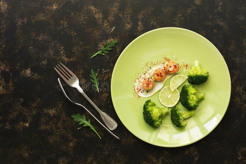 Przegrzebki z brokułami i wapnem w talerzu na ciemnym nieociosanym tle delikatny dietetyczne jedzenie zdrowe Odgórny widok, miesz fotografia royalty free