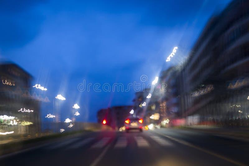 Przejście i samochód na nocy ulicie, zaświecającej zamazującymi cieniami i krzakami zdjęcie stock