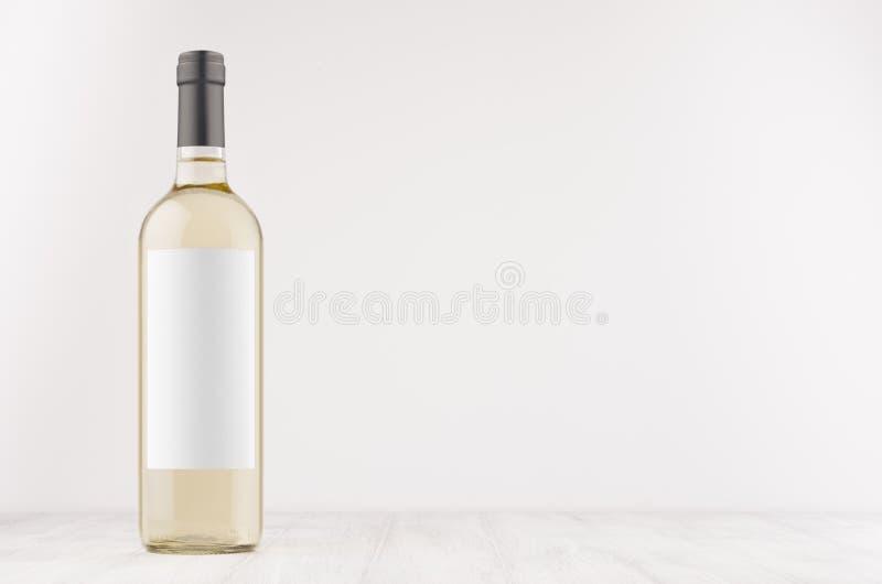 Przejrzysta białego wina butelka z pustą białą etykietką na białej drewnianej desce, wyśmiewa up fotografia stock