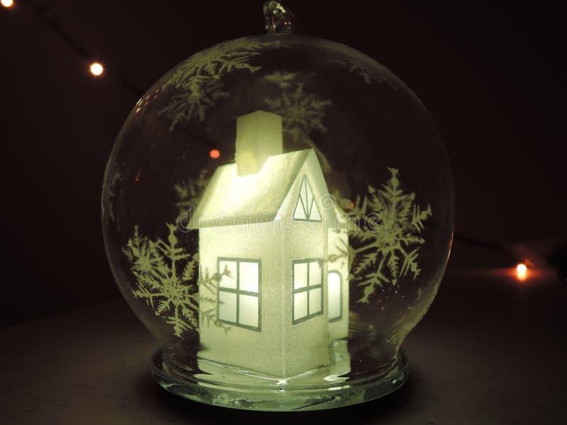 Przejrzysta Bożenarodzeniowa piłka wśrodku którego jest pięknego bielu domu rozjarzony światło białe wśrodku obraz stock