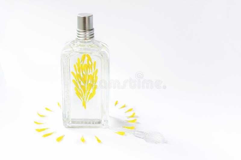 Przejrzysta pachnidło butelka na białym tle dekorującym z żółtymi kwiatów płatkami fotografia stock