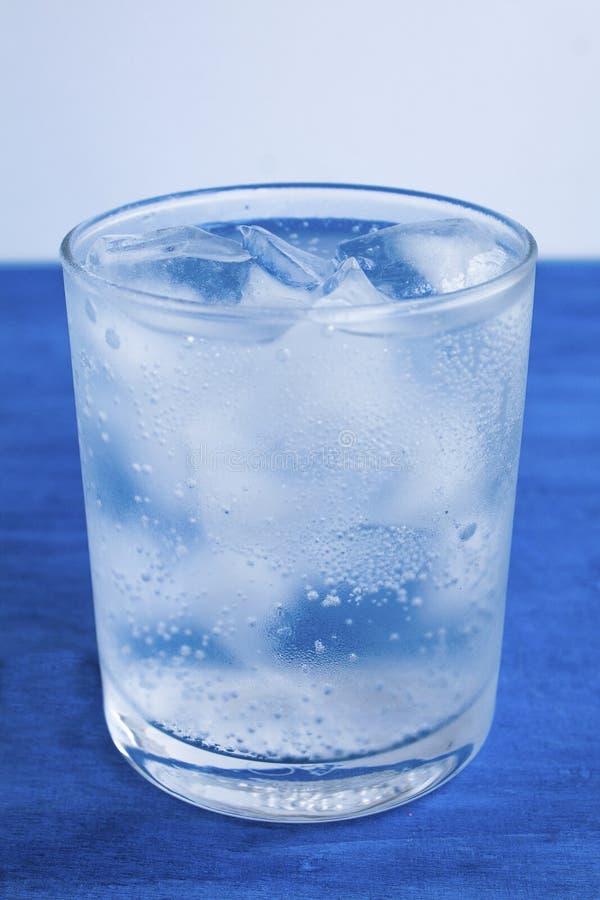 Przejrzysty szkło z wodą i kostka lodu na błękitnym tle obrazy royalty free