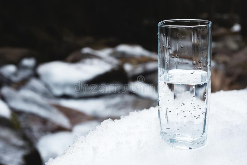 Przejrzysty szklany szkło z pić góry wody stojaki w śniegu przeciw tłu czysta halna rzeka fotografia royalty free