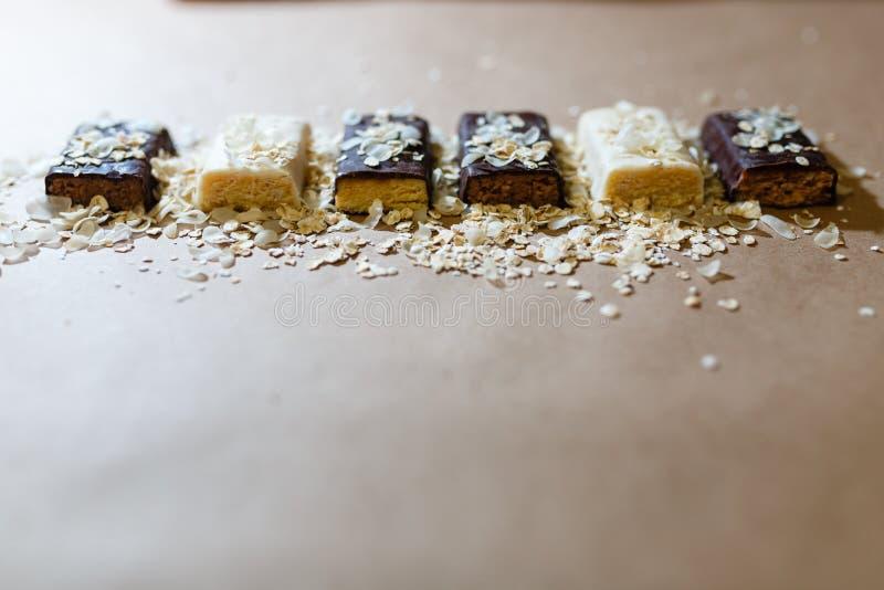 Przekąska czekoladowi proteinowi bary z różnymi smakami w kontekście kropią ryżowych płatki na pieczenie papierze, Teflon papier  obraz royalty free