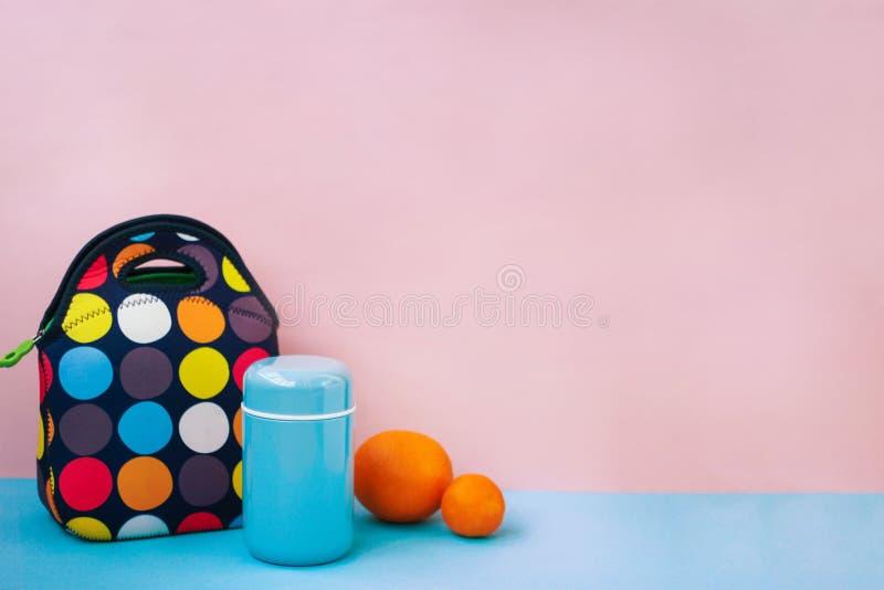 Przekąska na przerwie z lunchbox kolorowa torebka, błękitny termos, pomarańcze, tangerine miejsce dla teksta, różowy tło fotografia royalty free
