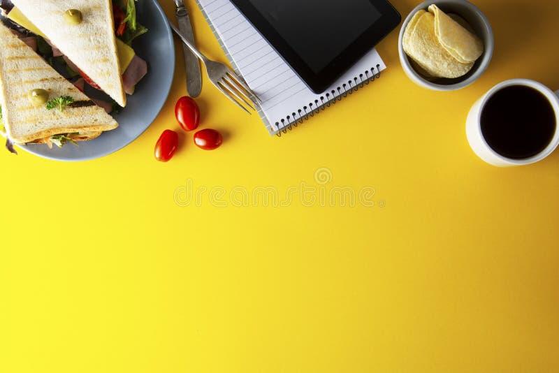 Przek?ski, fasta food poj?cie Eatting przy miejsce pracy ?wie?a ?wietlicowa kanapka, warzywa, kawa, frytki, s?odcy ciastka Pastyl fotografia royalty free
