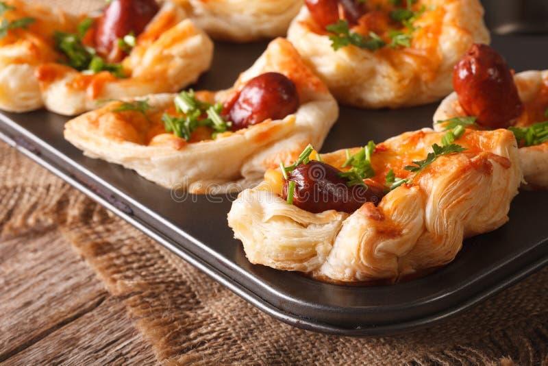 Przekąsza ptysiowe babeczki z kiełbasą, serem i cebulkowy makro- w wypiekowym d, fotografia royalty free