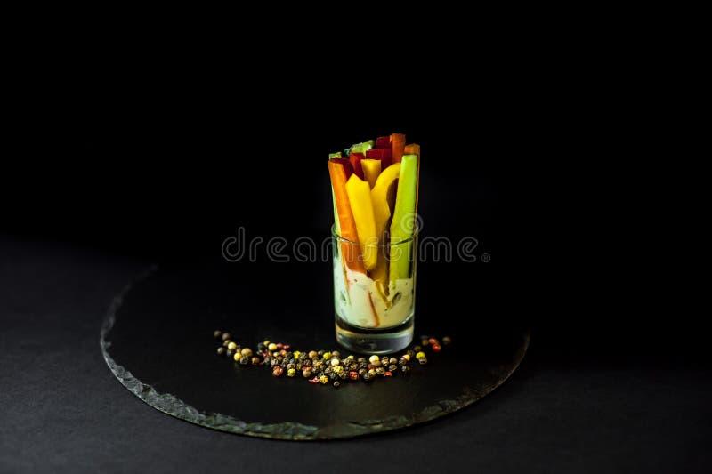 Przekąsza w szklanej filiżance na czarnym łupku Pieprze z kumberlandem obrazy stock