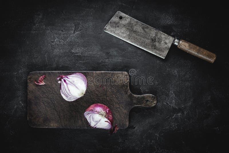 Przekrawająca Czerwona cebula na rocznik Tnącej desce z Mięsnym Cleaver fotografia stock