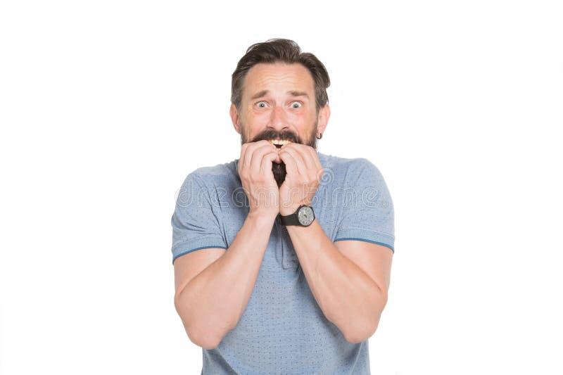 Przelękły brodaty mężczyzna gryźć jego gwoździe podczas gdy być nerwowy obraz stock