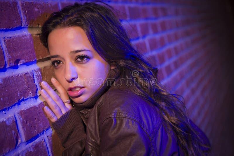 Przelękła Ładna młoda kobieta Przeciw ściana z cegieł przy nocą zdjęcie stock