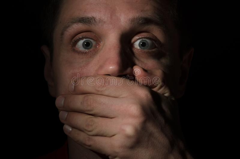 Przelękła twarz mężczyzna z oczami horror który siłą zakrywał jego usta z jego ręką pełno, odizolowywał na czarnym tle zdjęcia royalty free