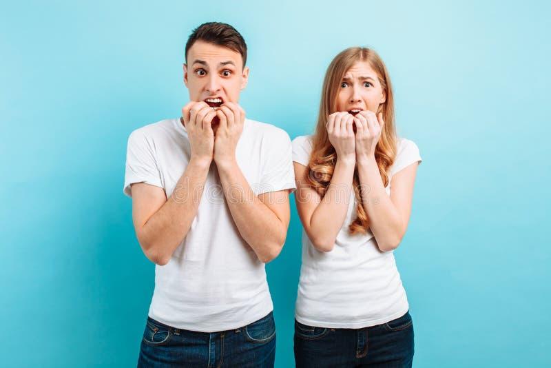 Przelękły mężczyzna i kobieta trzyma ręki blisko usta młoda para, przestraszyliśmy wyrażenia, na błękitnym tle obrazy royalty free