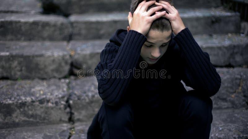 Przelękły osamotniony chłopiec obsiadanie na starych krakingowych krokach, echa wojna, żal w życiu obrazy royalty free