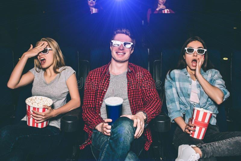 Przelękli i zmartwioni nastolatkowie są siedzący filmy i oglądający Dziewczyny próbują no widzieć jaki ` s iść na ekranie obrazy stock