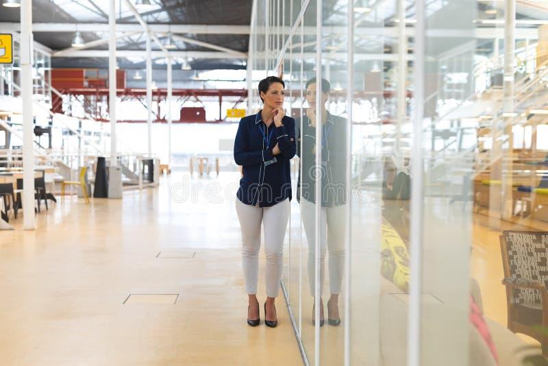 Przemyślana biznesmenka opierająca się na szklanej ścianie i rozglądająca się w nowoczesnym biurze obrazy royalty free