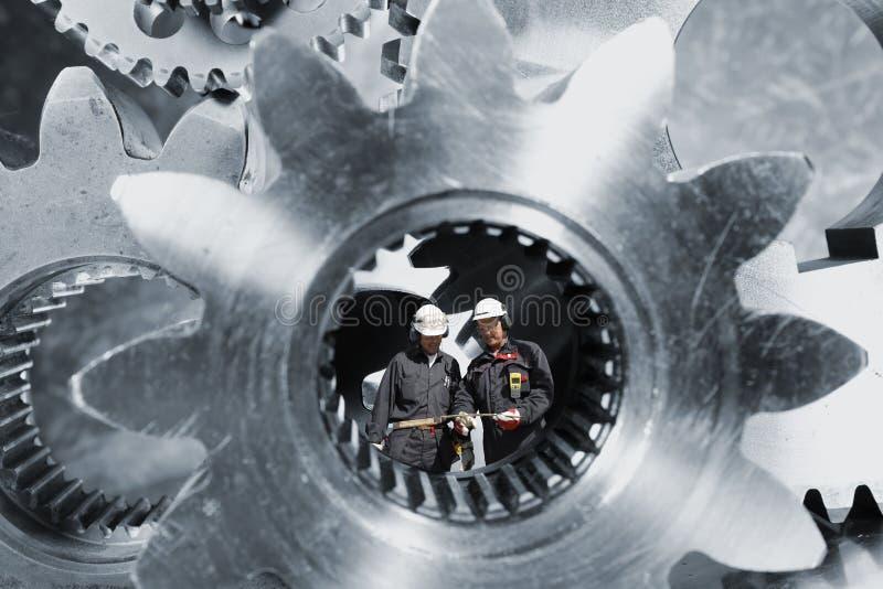Przemysłów pracownicy wśrodku gigantycznych cogs axles zdjęcia royalty free