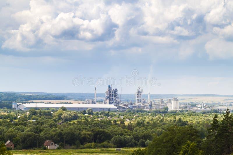 Przemysłowa cementowa fabryka z drymbami dymi i bufiastymi chmurami ab obraz royalty free
