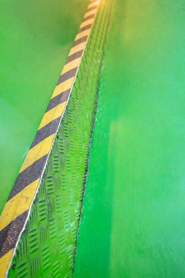 Przemysłowa pasiasta droga lub kroka ostrzeżenie na zielonym przejściu fotografia royalty free