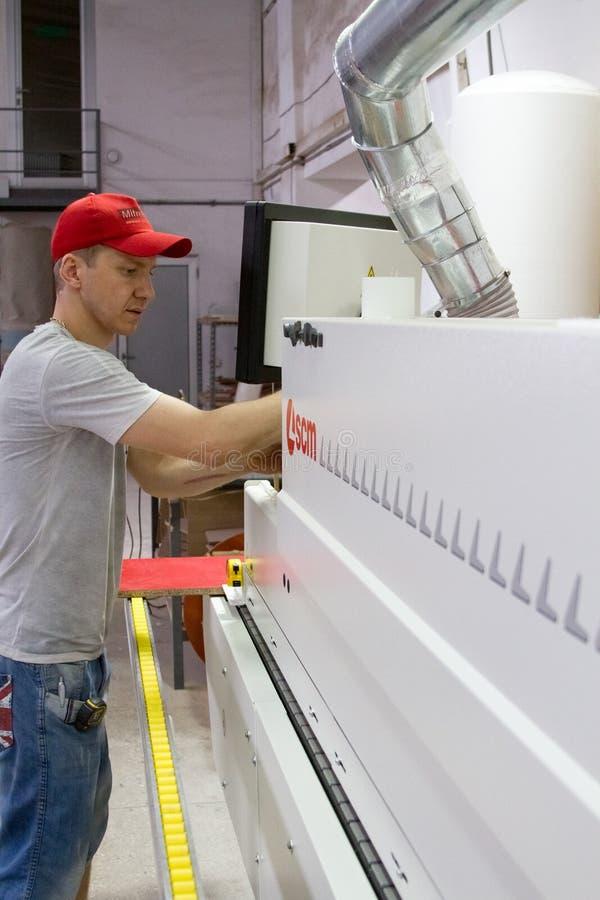 Przemysłowego cieśli pracownika operacyjna drewniana tnąca maszyna podczas drewnianej drzwiowej meblarskiej produkci fotografia royalty free