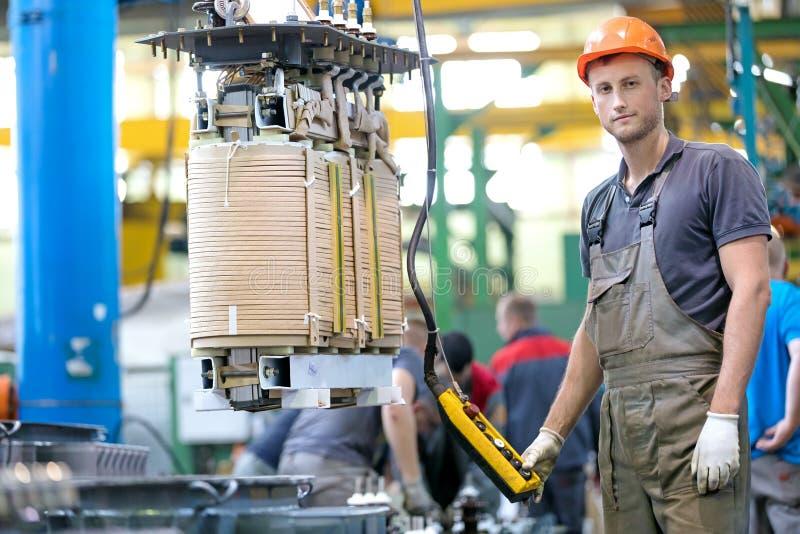 Przemysłowego pracownika władzy gromadzić transformator przy konwejer fabryki warsztatem fotografia royalty free