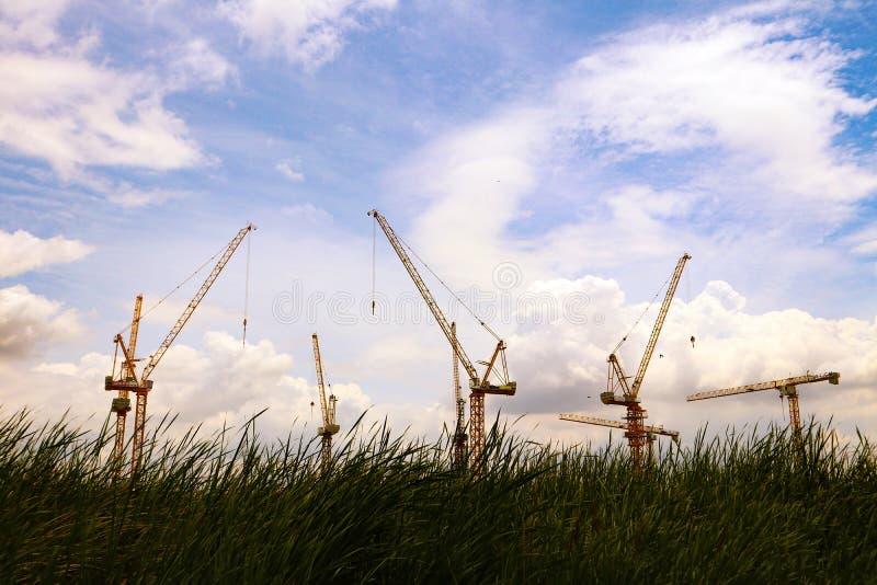 Przemysłowi budowa żurawie i kondominium budynek na niebieskim niebie zdjęcie stock