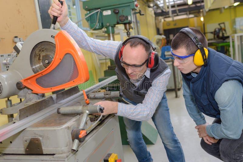 Przemysłowi pracownicy używa metalu krajacza maszynę obrazy royalty free