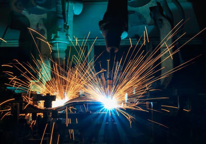 Przemysłowi spawalniczy roboty są ruchu spawem w linii produkcyjnej zdjęcie stock