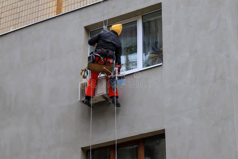 Przemysłowy arywista kończy ścianę budynek Mężczyzna wiesza na arkanach na fasadzie drapacz chmur fotografia stock