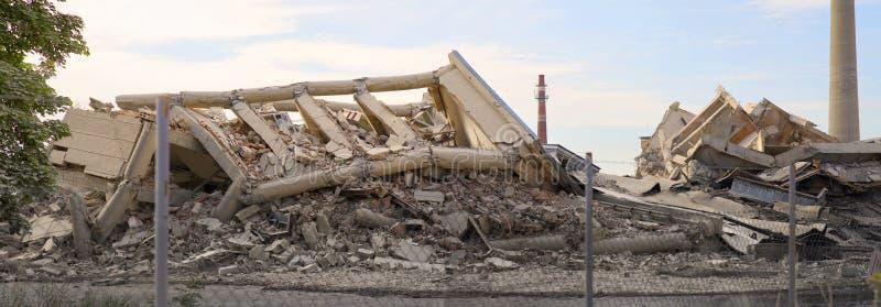 Przemysłowy betonowy budynek za ogrodzeniem destructed strajkiem Katastrofy scena pełno gruzy, pył i rozbijający zdjęcia stock
