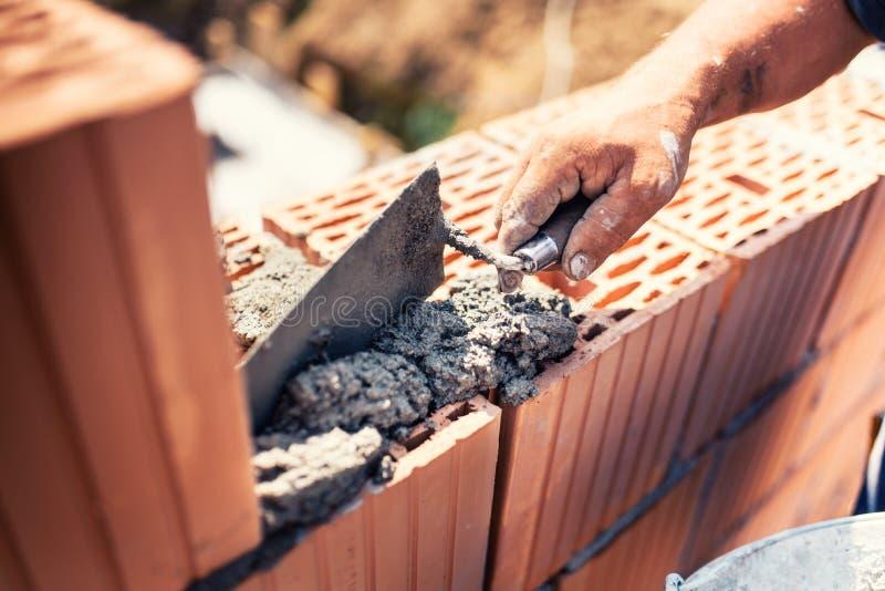 Przemysłowy - budowa murarza pracownika budynku ściany z cegieł, moździerza i kitu nożem, zdjęcia royalty free