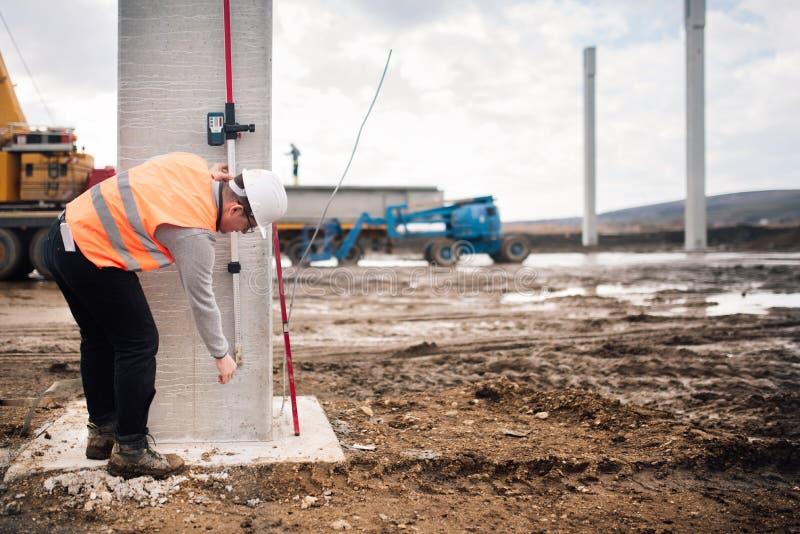 Przemysłowy inżynier pracuje na placu budowy z cementowymi filarami i przegląda narzędzia zdjęcie royalty free